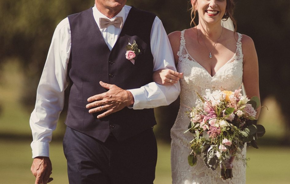 father and bride walking down aisle on capser country club golf course
