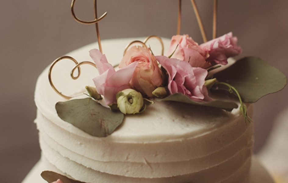white and floral cake with j and n initials