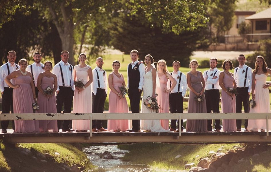 bridal party standing on bridge over creek