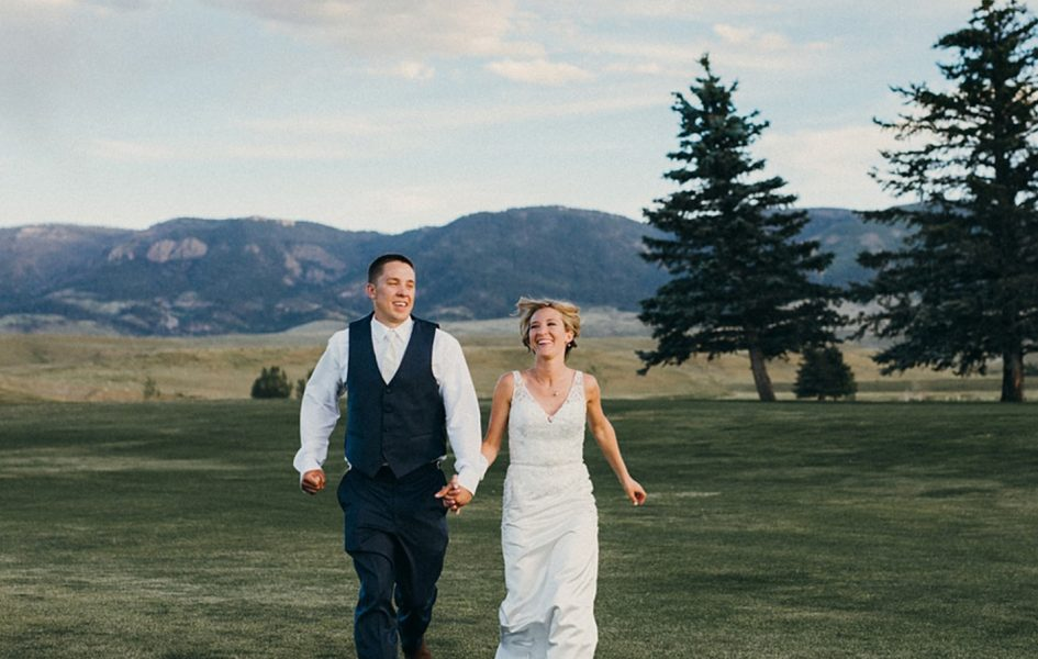 bride and groom running on casper country club golf course