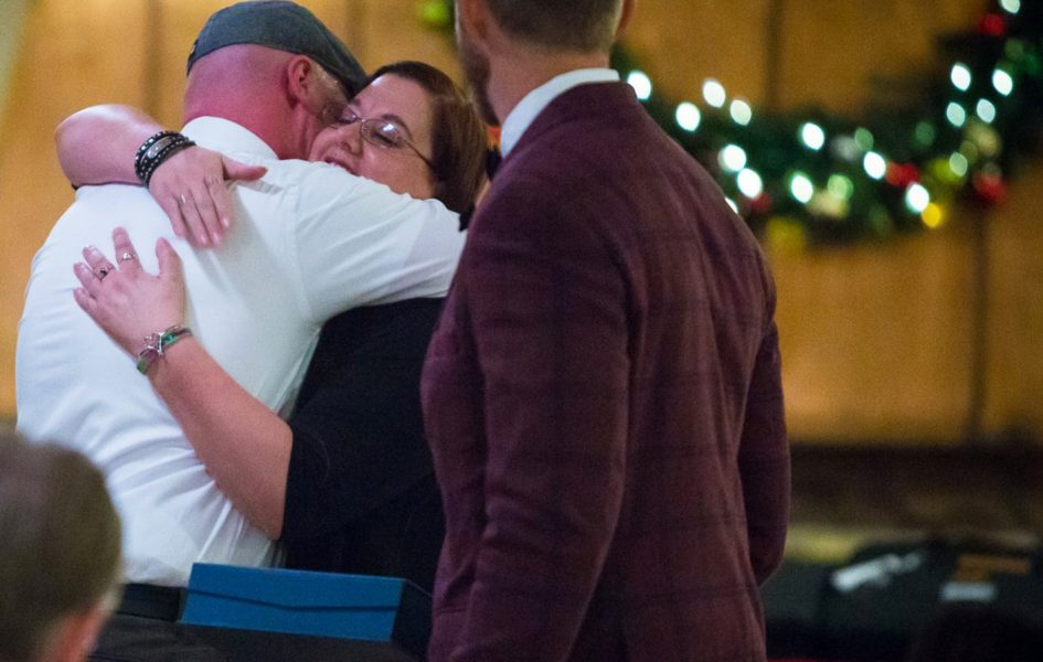 coldwell employees hugging at holiday party