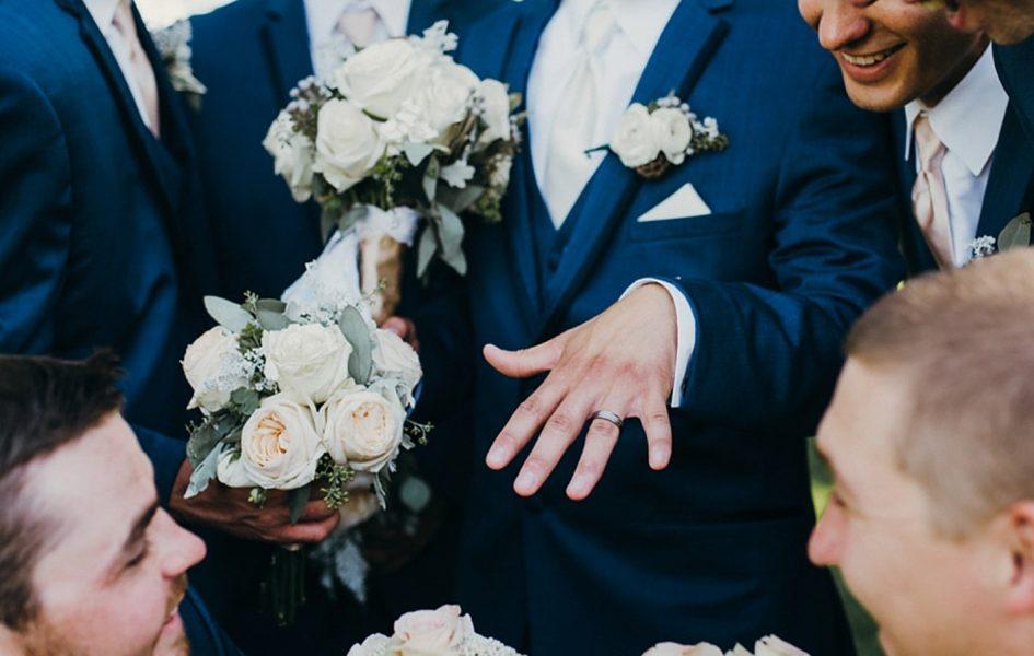 groomsmen looking at groom's new ring