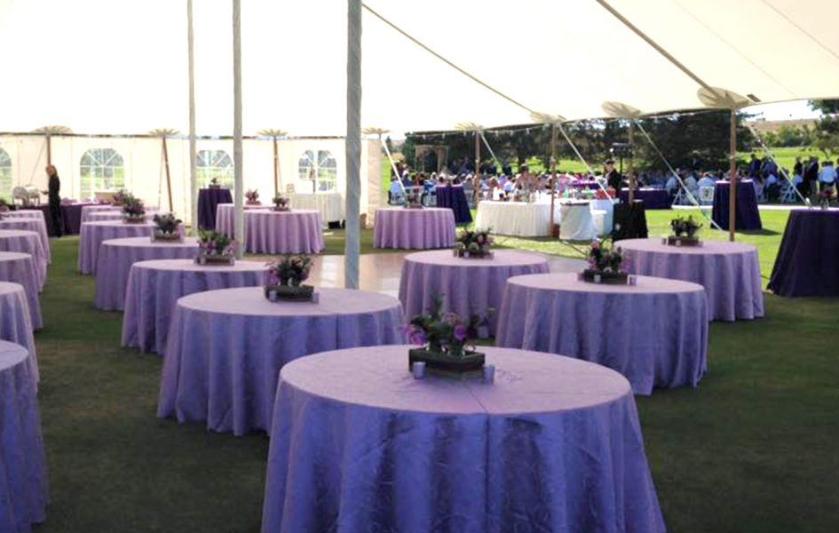 tables set with purple table cloths and flowers