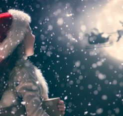 little girl watching santa and his reindeers in the sky