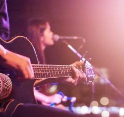 gentleman and woman playing the guitar and singing on stage