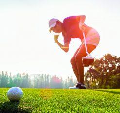 lady golfer watching her ball land near hole
