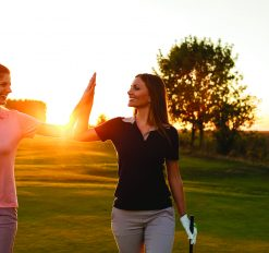 Shot of two female golfers giving high five on the golf course